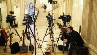 A member of the media waits in the great hall at Parliament Buildings, Stormont, near Belfast Tuesday, Dec. 23, 2014.