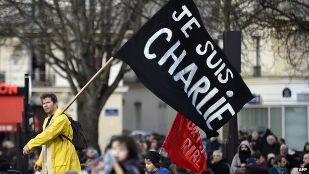 A man waves a flag reading 'Je suis Charlie' during a unity rally in Paris. Photo: 11 January 2015