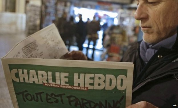 Jean Paul Bierlein reads the new Charlie Hebdo outside a newsstand in Nice, southeastern France, 14 January 2015