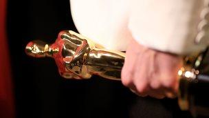 Oscar statue in hand