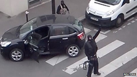The Kouachi brothers gesture as they return to their car after the attack outside the offices of French satirical weekly newspaper Charlie Hebdo