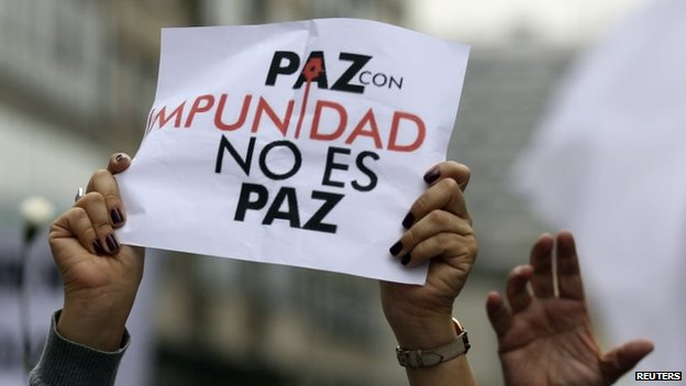 "A protesters holds up a sign that reads, ""Peace with impunity is not peace"" during a demonstration in Bogota on 13 December, 2014."