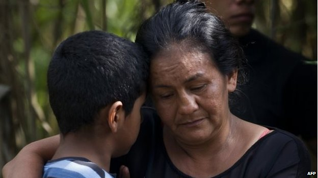 A woman embraces a child as the corpses of five soldiers killed by the Farc are removed in a rural area of Santander de Quilichao on 19 December, 2014