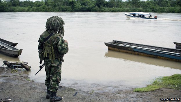 A soldier stands guard on the banks of the Atrato river on 19 November 2014