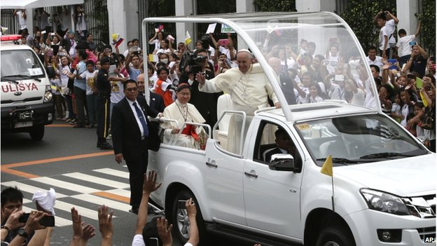 Pope Francis waves to the faithful from his Popemobile as his motorcade leaves the Presidential Palace for the Manila Cathedral Friday, 16 January 2015 in Manila, Philippines.