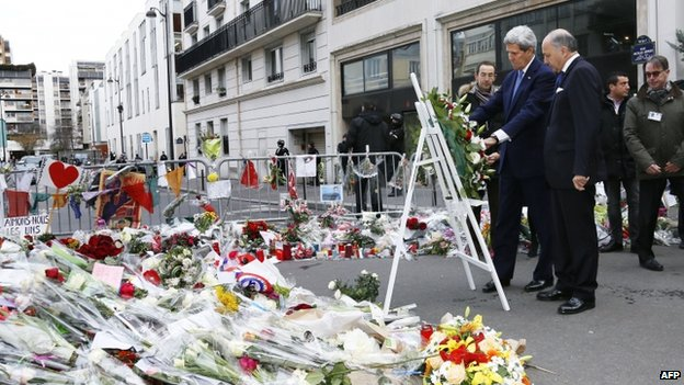 US Secretary of State John Kerry (C) and French Foreign Affairs minister Laurent Fabius lay a wreath of flower to pay tribute to the victims killed in the attack of the satirical newspaper Charlie Hebdo