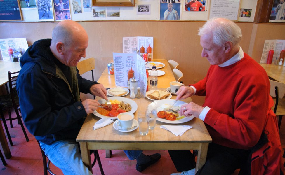 Two gentlemen eat breakfast at Alpino cafe, Islington, London