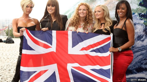 The Spice Girls hold up a British flag.