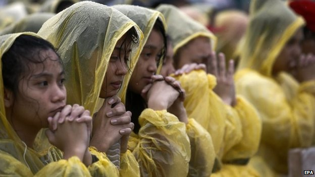 People pray for the victims of Typhoon Haiyan during the Mass in Tacloban