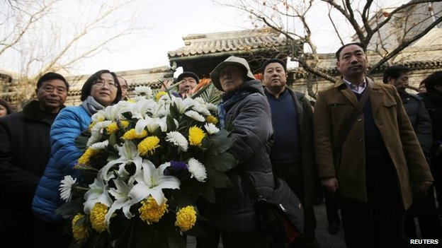 Mourners bring a bouquet of flowers as they visit the house of Zhao Ziyang on the 10th anniversary of his death in Beijing, 17 January 2015