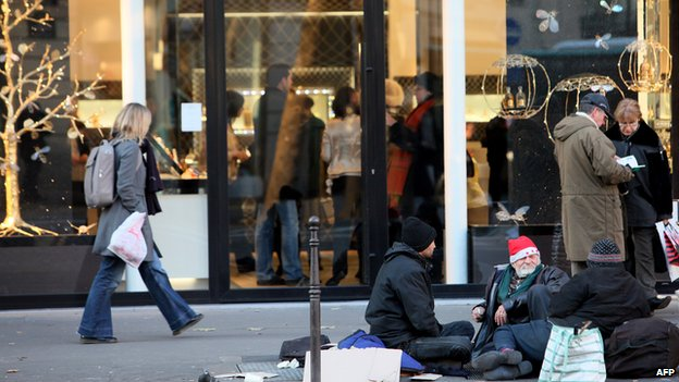 Homeless people beg in a street next to a luxury store in Paris