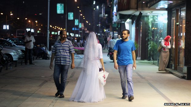 Samah Hamdi in her wedding dress walking down a street