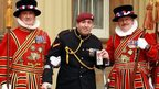 L/Bombardier Parkinson with members of the Yeoman of the Guard after receiving his MBE medal