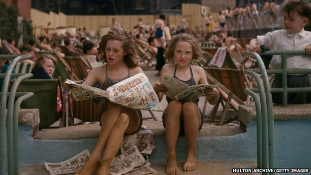 Two children read a newspaper in 1956