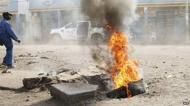 A man walks past a tyre set alight during a nation-wide protest as opposition parties tried to block a change in the law that may delay elections, in Goma eastern Democratic Republic of Congo (19 January 2015)