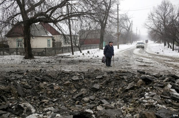 A man stands by a fresh crater in Debaltseve, Donetsk region, 20 January