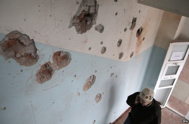A woman walks past a wall pocked with shrapnel at a hospital in the city of Donetsk, 20 January