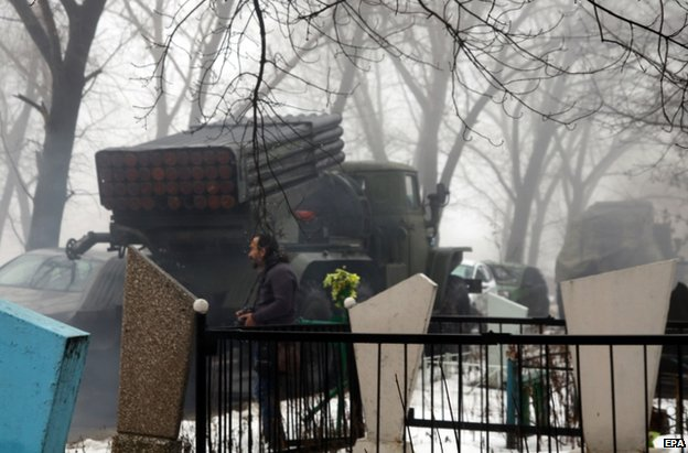A rebel rocket launcher stands beside a cemetery in Donetsk, 20 January