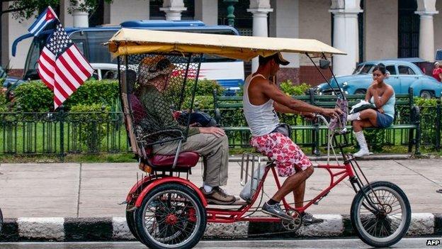 A pedicab with a US and a Cuban flag drives along a street of Havana on 16 January, 2015