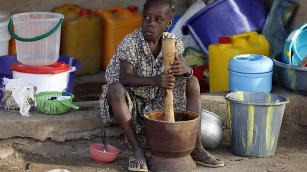 A girl displaced as a result of Boko Haram attacks in the northeast region of Nigeria, uses a mortar and pestle at a camp for internally displaced people in Yola, Adamawa State on 14 January 2015