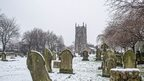 A graveyard covered in snow. Bare trees line the graveyard, a tall church stands in the background.