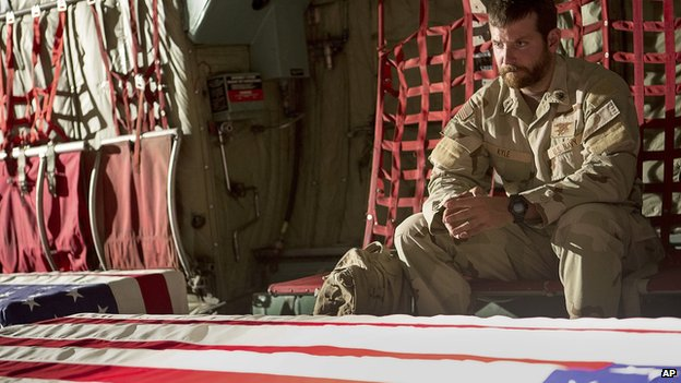 Chris Kyle, played by Bradley Cooper, sits next to flag-draped coffins in the film American Sniper
