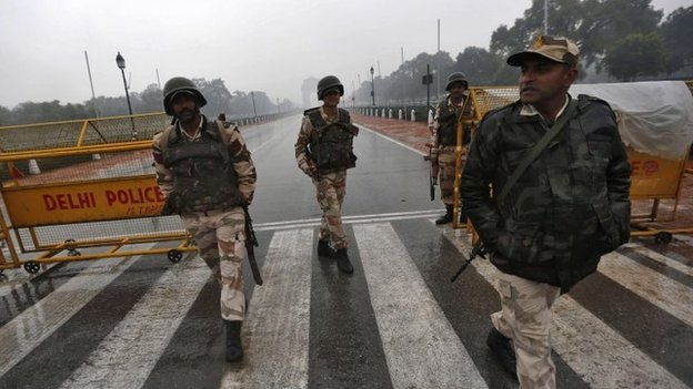 Indian security personnel keep guard in front of India Gate as it rains in New Delhi January 22, 2015.