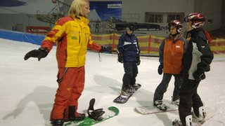 Snowboard instructor with three students at an indoor ski slope