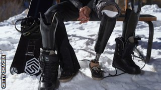 Amu Purdy's legs showing her artificial limb while sitting on a bench in the snow by her snowboard.