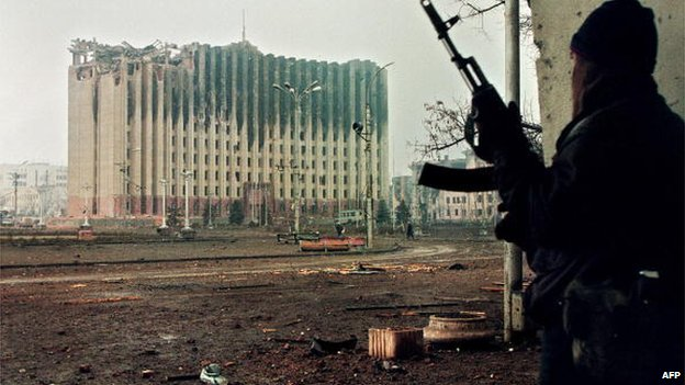 Picture taken on January 10, 1995 shows a Chechen fighter taking cover from sniper fire in a building across the square from the presidential palace destroyed by Russian artillery bombardments.