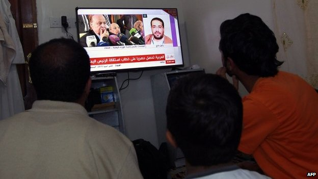 Men watch the news on a screen in Sanaa, 22 January
