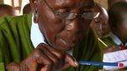 90-year-old Kenyan student Priscilla Sitienei  in school uniform, holding a pencil