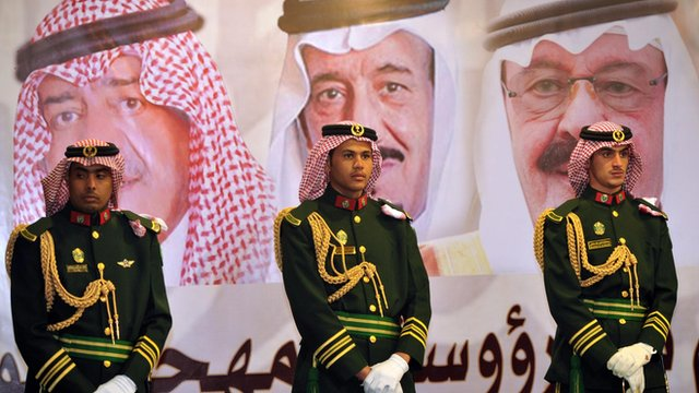 "Saudi royal guards stand on duty in front of portraits of King Abdullah bin Abdulaziz (R), Crown Prince Salman bin Abdulaziz (C) and second deputy Prime Minister Muqrin bin Abdulaziz during the traditional Saudi dance known as ""Arda"" at the Janadriya culture festival at Der""iya in Riyadh, in this file picture taken February 18, 2014"
