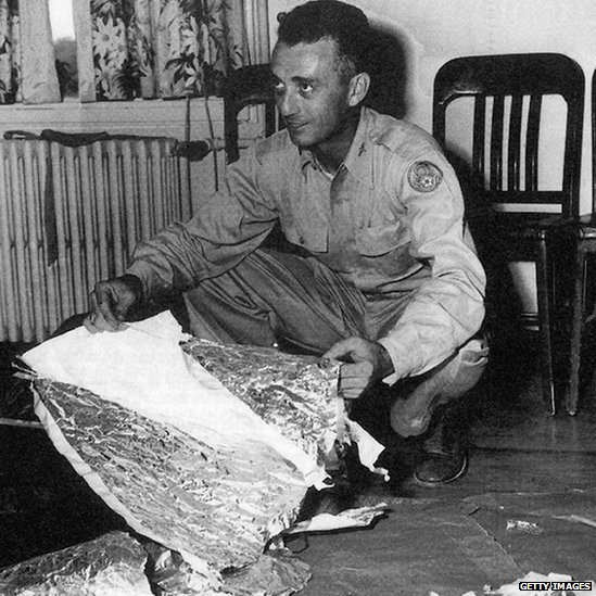 A photo of a US military officer holding wreckage