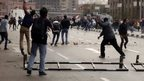 Anti-government protesters throw stones at pro-government protesters and police vehicles as police arrives to prevent anti-government protesters from entering Tahrir square in Cairo January 25, 2015.