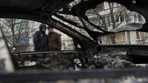 Local residents look at a burned car outside an apartment building in Mariupol, eastern Ukraine, on 25 January, 2015