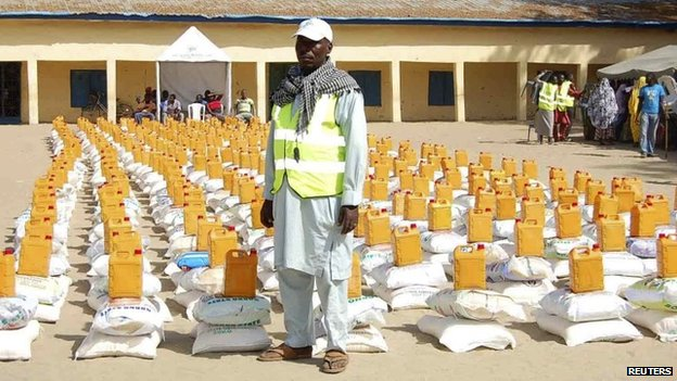 An official stands in front of relief materials at a camp for displaced people in Maiduguri in Borno State on 19 January 2015