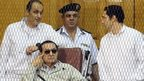 Gamal Mubarak (left) and Alaa Mubarak (right) in court with their father, Hosni Mubarak (14 September 2013)
