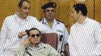 Gamal Mubarak (left) and Alaa Mubarak (right) in court with their father, Hosni Mubarak (14 September 2013)