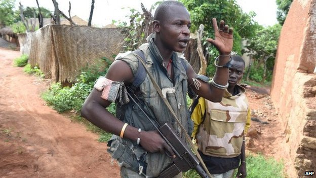 An armed anti-Balaka militiaman (C) gestures as he walks by houses allegedly destroyed by former Seleka militiamen in Bouca, some north of Bangui, on 25 April 2014