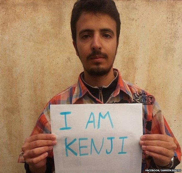 Photo of a man holding a placard that says 'I am Kenji'