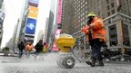 A worker spreads salt on the sidewalk in Times Square in preparation for a large winter storm in New York, New York, USA, 26 January 2015.