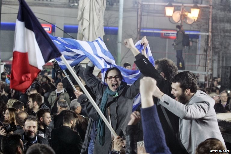A supporter of Alexis Tsipras, leader of Syriza left-wing party, holds the Greek and French flag