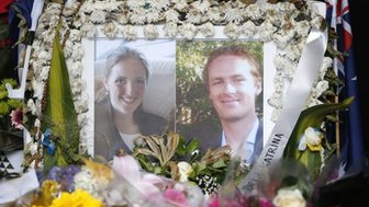 Photographs of Sydney's cafe siege victims, lawyer Katrina Dawson (L) and cafe manager Tori Johnson are displayed in a floral tribute near the site of the siege in Martin Place, 23 December 2014