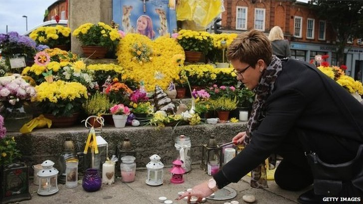 Flowers and messages of condolence besides the clock tower in Hanwell