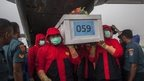 Indonesian rescue personnel unload a coffin bearing a body recovered from the underwater wreckage of ill-fated AirAsia flight QZ8501, on 23 January, 2015