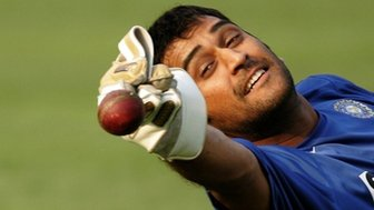 In this photograph taken on November 28, 2007, Indian wicketkeeper Mahendra Singh Dhoni tries to catch a ball during a training session at The Eden Gardens Stadium in Kolkata,