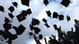 Students throwing mortarboards into the air