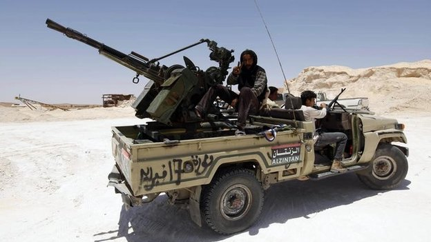 Rebel fighters sit in their truck on high ground overlooking the town of Bir Ghanam, about 100 km (62 miles) south of Tripoli, on 30 June  2011