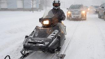 A man driving a snowmobile.